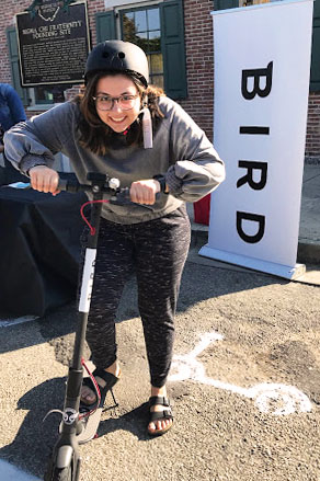 Miami student Clare DiCuccio, wearing a free helmet, tries out a Bird scooter last Saturday at High and East Park Streets, uptown. <em>Photo by Clare DiCuccio</em>