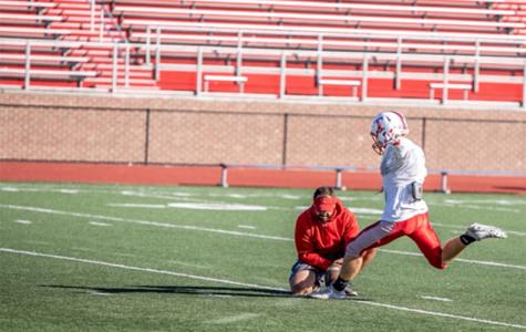 Coach J.D. Vonderheide holds the snap Oct. 24 for junior Tyler Engelhard, as he practices field goals. <em>Photo by Shelby Frieszell</em><br>