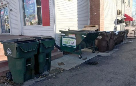 Recycling containers such as these, pushed up to the side of The Den and around the corner from Skipper's Pub & Top Deck, are scant on High Street. Uptown business owners have said that apartment dwellers dump trash into recycling bins. <em>Photo by Madeline Mitchell</em><br>