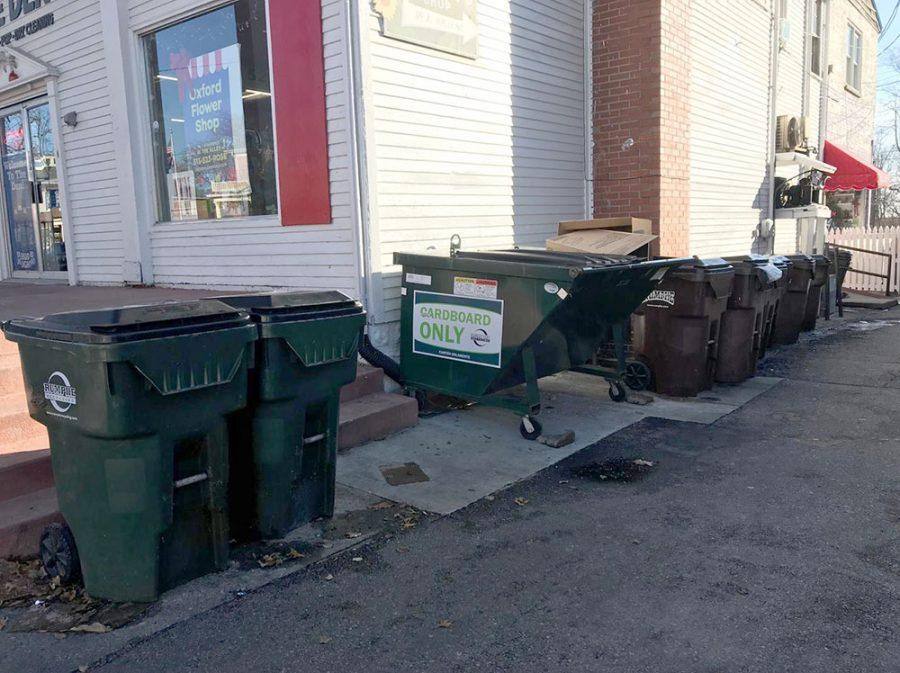 Recycling containers such as these, pushed up to the side of The Den and around the corner from Skipper's Pub & Top Deck, are scant on High Street. Uptown business owners have said that apartment dwellers dump trash into recycling bins. Photo by Madeline Mitchell