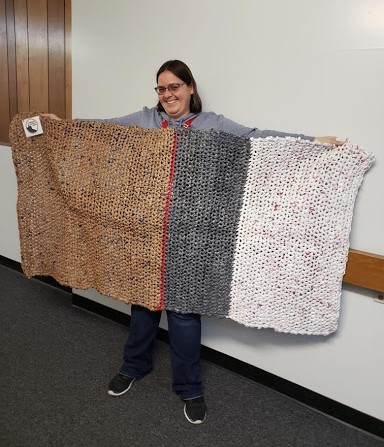 Karissa Uhl holds up a mat made of plastic grocery bags. Volunteers need about 800 bags to crochet one six-foot long mat. <em>Photo courtesy of Karissa Uhl</em><br>