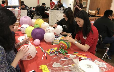 Students Olivia Lewis (left) and Tian Qi decorate paper lanterns with visiting international instructor Wenting Yang (far right). <em>Photo by Erin Glynn</em>