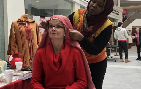 Helena Kabasele (right) helps Renate Crawford, Miami University ambassador, adjunct professor and wife of Miami President Gregory Crawford, try on a traditional hijab during the World Hijab Day celebration. Photo by <em>Leanne Stahulak</em>