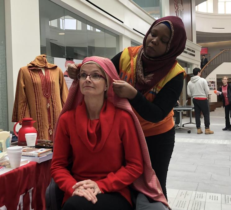 Helena Kabasele (right) helps Renate Crawford, Miami University ambassador, adjunct professor and wife of Miami President Gregory Crawford, try on a traditional hijab during the World Hijab Day celebration. Photo by Leanne Stahulak