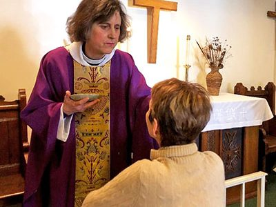 Reverend Sara Palmer at Holy Trinity Episcopal Church spreads the ashes on congregation member Ellen Reister's forehead after the Ash Wednesday service on March 6. <em>Photo by Leanne Stahulak.</em>