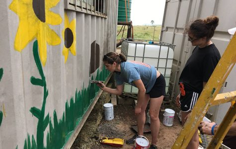 Crossroads volunteer Dani Stelzer (left) paints a mural on the outside of a shipping container turned into a pre-school, as Katie Coverdale (right) observes the mural as a whole. <em>Photo provided by Katie Coverdale</em>