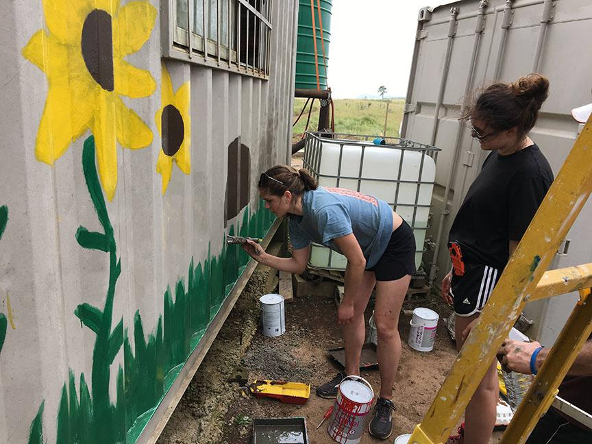 Crossroads volunteer Dani Stelzer (left) paints a mural on the outside of a shipping container turned into a pre-school, as Katie Coverdale (right) observes the mural as a whole. Photo provided by Katie Coverdale