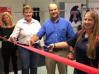 Officers in the Talawanda Athletic Boosters Angie James, Bonnie Norris and Dave Krausher join Talawanda Middle School Athletic Director Annie Klenk in cutting the ribbon to dedicate the middle school fitness and weight room in 2018. <em>Photo courtesy of the Talawanda Athletic Boosters</em><br>‍<br>