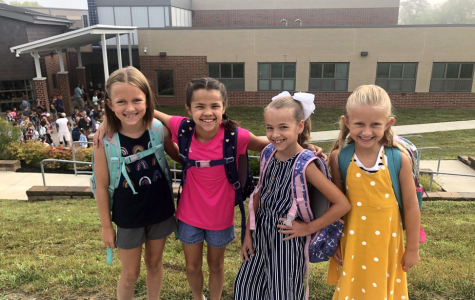 Students Ezra Pechan-Keeton, Brooklyn Porchowsky, Ellie Porchowsky, and Mira Pechan-Keeton pose for pictures in front of Kramer Elementary on the first day of school Wednesday. Photo by Halie Barger