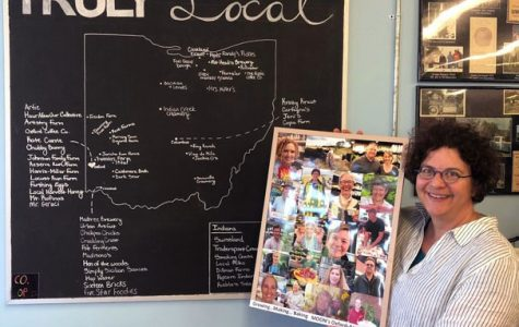 Bernadette Unger standing by a chalkboard map that shows where the produce comes from that she sells at Oxford's MOON Co-Op. <em>Photo by Marguerite Meyers</em>