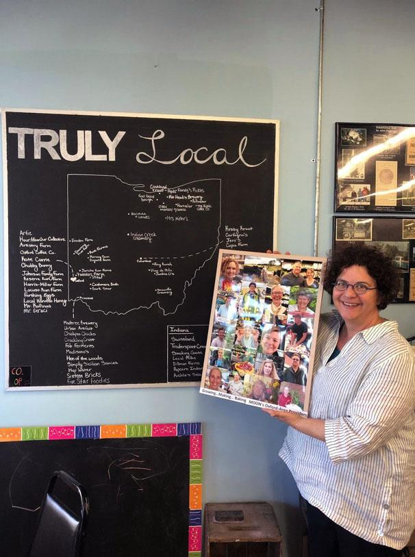 Bernadette+Unger+standing+by+a+chalkboard+map+that+shows+where+the+produce+comes+from+that+she+sells+at+Oxford%E2%80%99s+MOON+Co-Op.+Photo+by+Marguerite+Meyers
