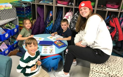 First graders at Kramer Elementary (left to right) Jazzy Virk Tiago Motta and John Cerillo, learn Spanish phrases from Chloe Newsom, a student in a Miami conversational Spanish class. <em>Photo by Aaron Smith</em><br>