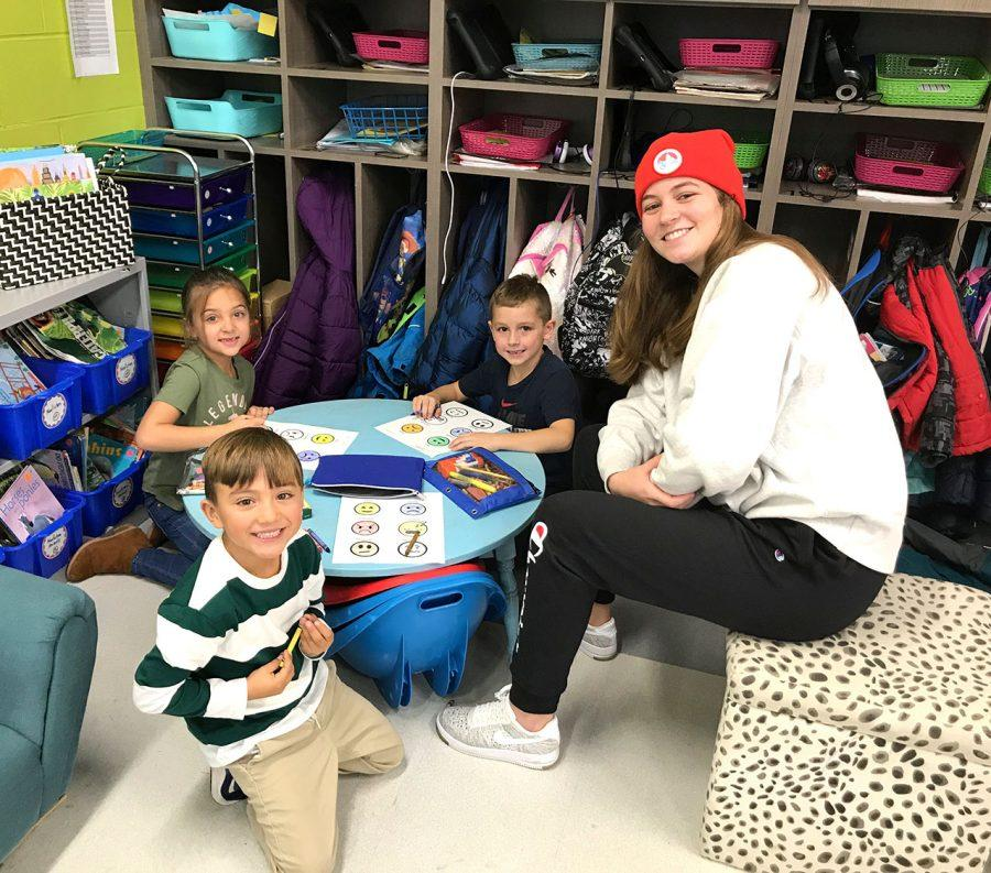 First graders at Kramer Elementary (left to right) Jazzy Virk Tiago Motta and John Cerillo, learn Spanish phrases from Chloe Newsom, a student in a Miami conversational Spanish class. Photo by Aaron Smith