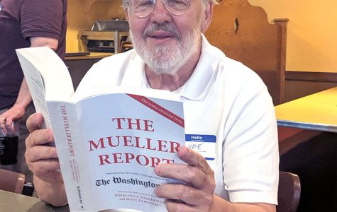 Clyde Brown, reading the report on the Mueller Investigation of the Trump administration while attending a Democratic Debate watching party in Oxford last June. <em>Observer file photo</em>