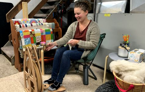 "McQuigg spinning yarn on her wheel. A largely self-taught ""fiber artist,"" she says she works ""sheep to sweater."" <em>Photo by Lexi Scherzinger</em>"