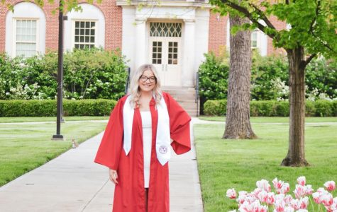 Halie Barger, a graduating Miami senior and member of the Observer staff, seen here in front of Kreger Hall, was one of many students who donned graduation robes and posed for a final school picture on campus this week. <em>Photo provided by Halie Barger</em><br>