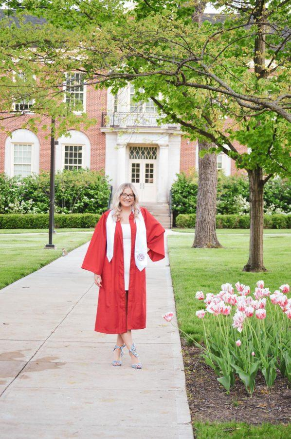 Halie Barger, a graduating Miami senior and member of the Observer staff, seen here in front of Kreger Hall, was one of many students who donned graduation robes and posed for a final school picture on campus this week. Photo provided by Halie Barger