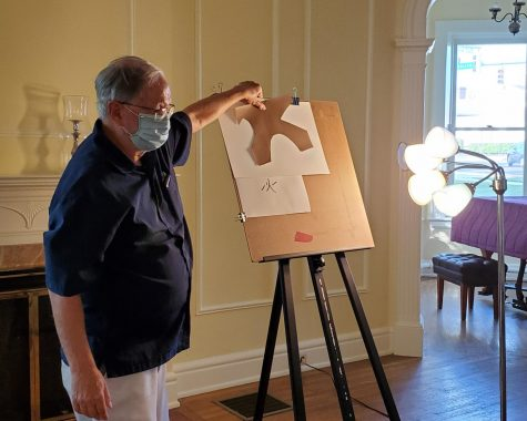 Howard Krauss, a local watercolor artist, teaches his class while wearing a mask