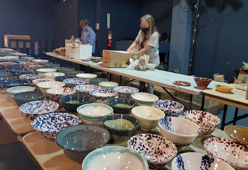 Volunteers set up handmade bowls for the Empty Bowls online sale.