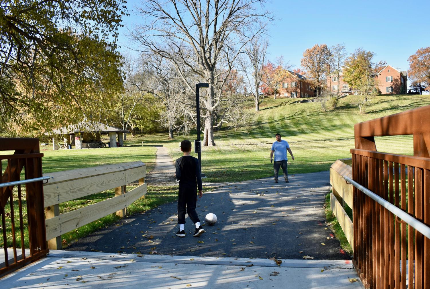 Jared Coffin (right) kicks a ball around with younger brother Isaac at the Peffer Park bridge, the site depicted in his mural.