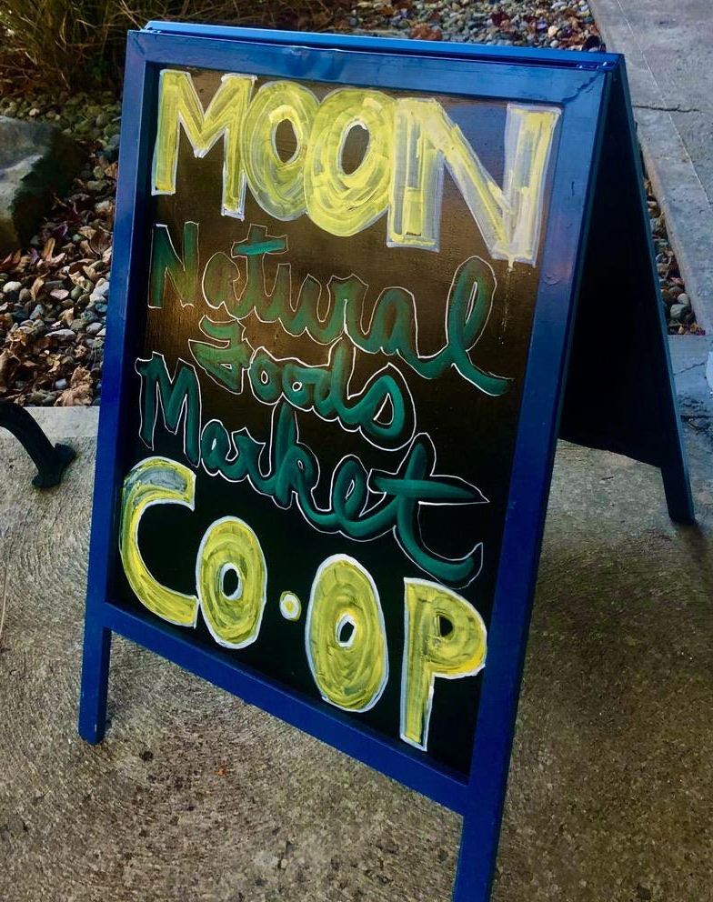 The sidewalk sign board welcomes passerby into MOON Co-Op. Photo by Camryn Smith