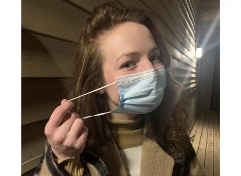Miami student Allie Brown demonstrates the double masking now being recommended as a precaution against new, more transmissible variants of COVID-19. Step #1: Brown puts on a standard paper medical-style mask.