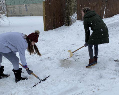 Emily Stegmeyer (left) and Shannon Allen shovel out Thursday morning at their house on Church Street.