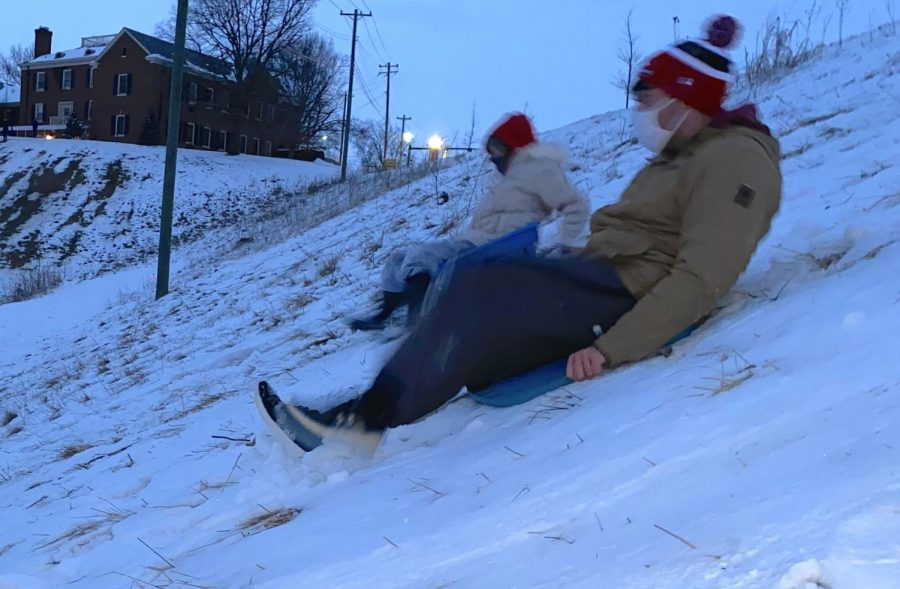Snow can be fun too, as Miami students Jacob Terwilleger and Meredith Horn can attest as they slide down the Peffer Park hill on makeshift sleds late Wednesday.