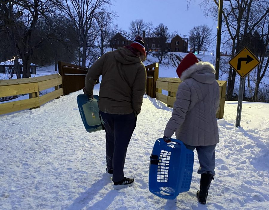 acob Terwilleger (left) prepares to use the lid from a storage bin to go sledding, while Meredith Horn prefers a laundry basket to sled down the hill at Peffer Park on Wednesday.