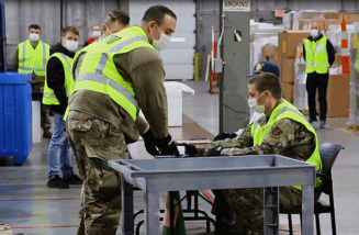 Ohio Gov. Mike DeWine says the widening availability of COVID-19 vaccines is helping end the pandemic. Here, members of the Ohio National Guard in Columbus pack up doses of vaccine for distribution around the state.