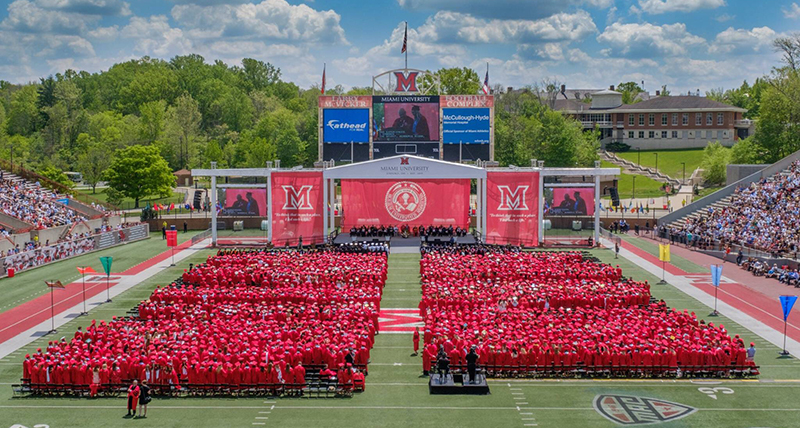 In the past year, as shown in this scene from the 2018 spring commencement, red-gowned graduates of Miami University crowd the field of Yager Stadium at graduation. Last year the pandemic forced the ceremony to be virtual, but May 14 through May 16, the graduates will return to Yager for their commencements.