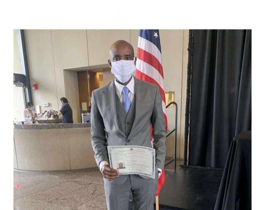Godwin+Agaba+holds+his+naturalization+certificate+the+day+he+took+his+oath+of+citizenship+on+Feb.+8%2C+at+Sinclair+Community+College+in+Dayton.