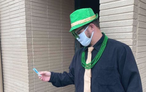 Brian Urell on Green Beer Day 2021, in one of many eccentric outfits for special holidays and popular drinking occasions, while checking IDs as a doorman at local bars.