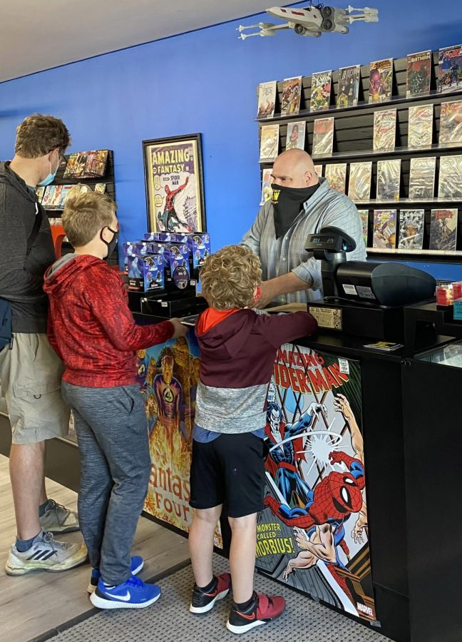 Future Great Comics owner Brian Levick rings up customers at the store's May 1 grand opening.