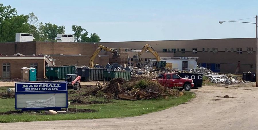 Dumpsters are being filled with the remains of the old Marshall Elementary School this summer. The new, almost finished school that will replace it, can be seen in the background.
