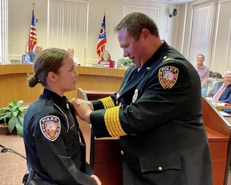 Oxford Police Chief John Jones pins the badge on Brooke Hartwig, newest officer on the city police force, at the June 15 meeting of city council.