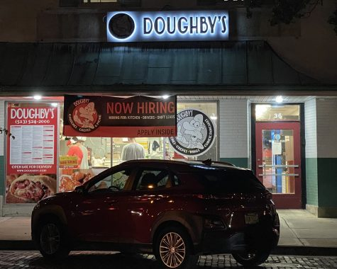 """The """"Now Hiring"""" sign is the most prominent display in the window of Doughby's, a popular High Street eatery that can't get enough help."""
