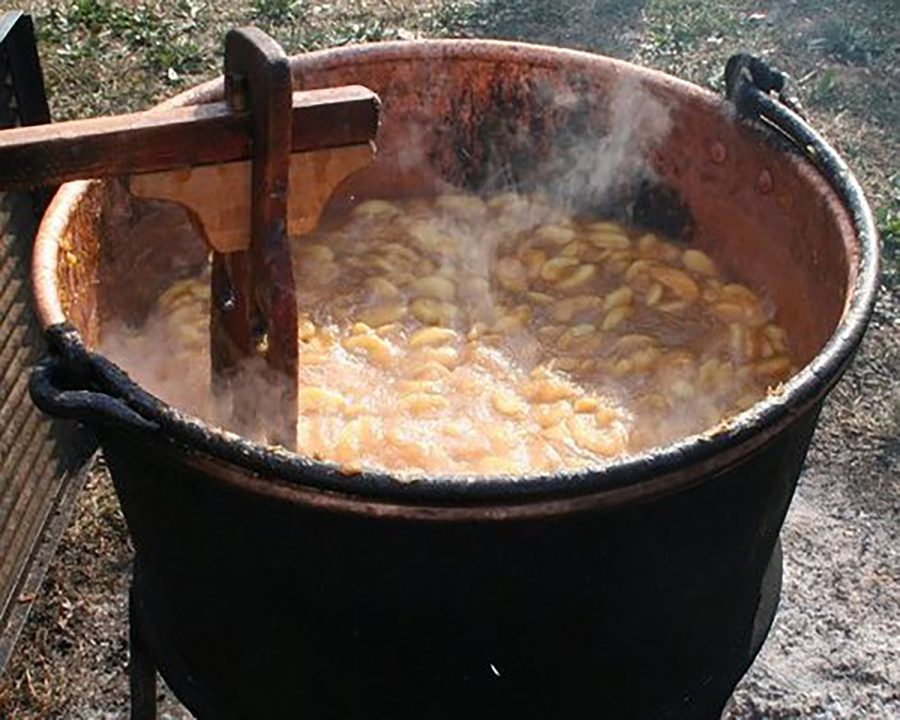 In this scene from the 2019 festival, apple butter is cooked the pioneer way, simmered and stirred in a huge copper kettle.