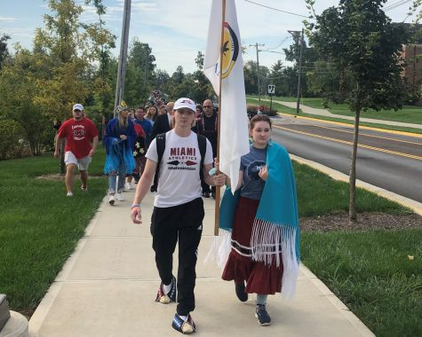Senior Josh McCoy and Junior Emma Fanning, both Myaamia Heritage students, carry the Miami Tribe flag, leading the walk of reflection.